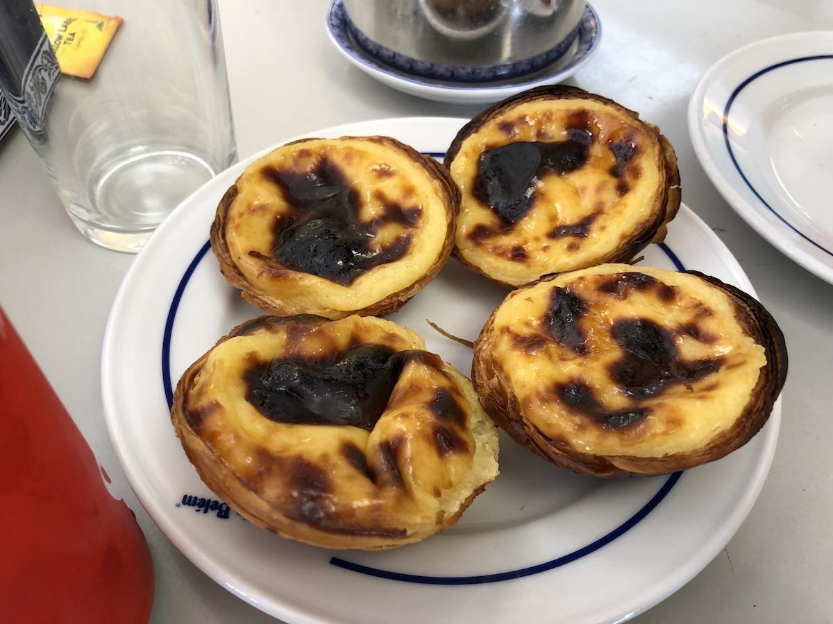 four custard tarts aka pasteis de Belem on a plate