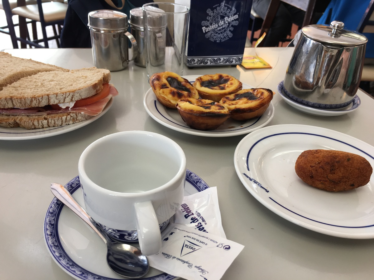 Table in a café with teapot and cup, sandwich, cod cake and pasteis de belem