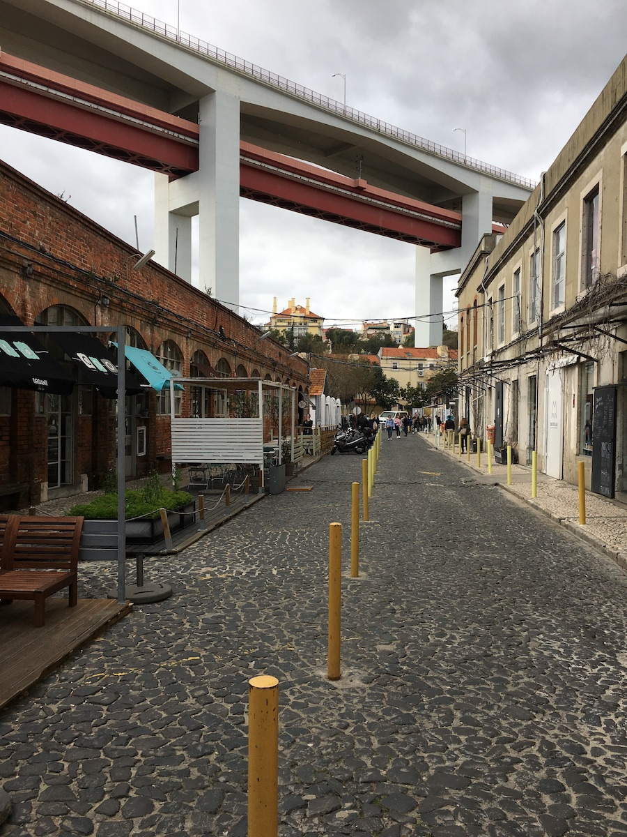 street with old factory building and bridge in background