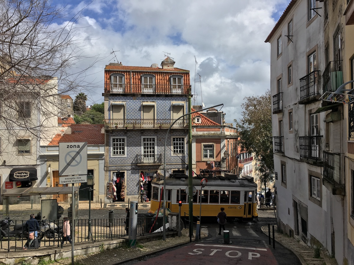 Street view in Lisbon with tram, people, old buildings