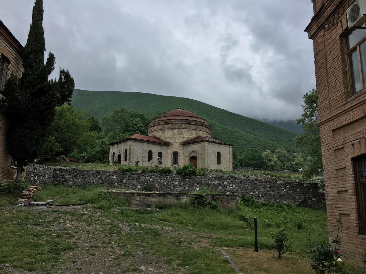 Runde Kirche vor bewaldetem Bergpanorama